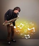 Przystojny muzyk bawić się na saksofonie z muzykalnymi notatkami Zdjęcia Royalty Free