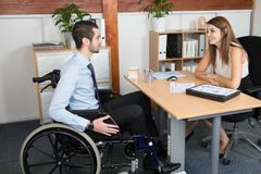 Przystojny niepełnosprawny biznesmen w wózku inwalidzkim przy jego biurem przed piękną młodą kobietą obraz stock
