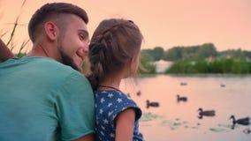 Przystojny ojciec siedzi z jego małą córką blisko jeziora i zegarka kaczek, rozmowa, zmierzch, rodzinny pojęcie zbiory wideo