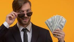Przystojny oligarcha w okularach przeciwsłonecznych pokazuje dolary i mruga, bogactwo, w górę zbiory