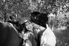 Przystojny, piękny kowboj, i cowgirl dobieramy się z koniem, comberem na rancho mieniu i całowaniem na rancho obraz stock