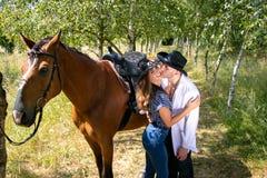 Przystojny, piękny kowboj, i cowgirl dobieramy się z koniem, comberem na rancho mieniu i całowaniem na rancho obrazy royalty free