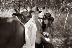 Przystojny, piękny kowboj, i cowgirl dobieramy się z koniem, comberem na rancho mieniu i całowaniem na rancho zdjęcia stock