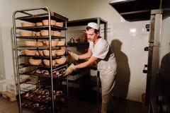 Przystojny piekarz w jednolitej mienie tacy pełno świeżo piec chleb przy produkcją Obrazy Stock