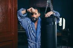 Przystojny pijący mężczyzna opiera na uderza pięścią bokserskiej torbie zdjęcie stock