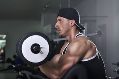 Przystojny potężny sportowy mężczyzna robi bicepsom ćwiczy z barbell Obraz Stock