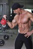 Przystojny potężny sportowy mężczyzna robi bicepsom ćwiczy z czajnika dzwonem Fotografia Royalty Free