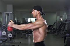 Przystojny potężny sportowy mężczyzna robi naramiennemu ćwiczeniu z czajnika dzwonem Obraz Royalty Free