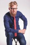Przystojny potomstwo mody mężczyzna obsiadanie na stolec podczas gdy Fotografia Royalty Free