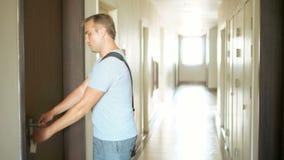 Przystojny poważny mężczyzna w popielatej koszulce otwiera drzwi z kluczami i wchodzić do jego mieszkanie zbiory