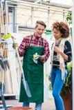 Przystojny pracownik pomaga klienta z wybierać ogrodnictwa narzędzie zdjęcie stock
