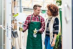 Przystojny pracownik pomaga klienta z wybierać ogrodnictwa narzędzie zdjęcie royalty free