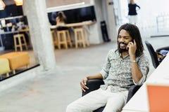 Przystojny projektant ono uśmiecha się podczas gdy pracujący w biurze obrazy stock