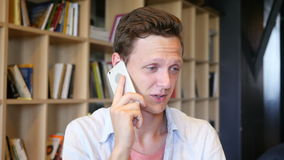 Przystojny przypadkowy uczeń opowiada na telefonie, ono uśmiecha się zdjęcie wideo