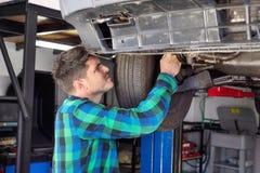 Przystojny samochodowy mechanik sprawdza zawieszenie system podnoszący samochód przy remontowym stacja obsługi fotografia royalty free