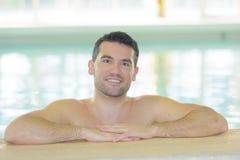 Przystojny seksowny mężczyzna w pływackim basenie obraz stock