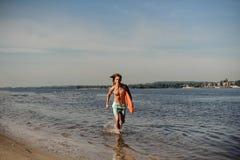 Przystojny seksowny plażowy ratownika bieg wzdłuż brzeg rzeki z Fotografia Royalty Free