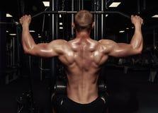 Przystojny silny sportowy mężczyzna pompuje up tylnych mięśnie Mięśniowy bodybuilder z nagą sport półpostacią robi ćwiczeniom w g zdjęcia stock