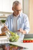 Przystojny skoncentrowany dorośleć mężczyzna kulinarną sałatkową używa pastylkę zdjęcie stock