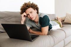 Przystojny skoncentrowany mężczyzna kłama na kanapie używać laptop obraz royalty free