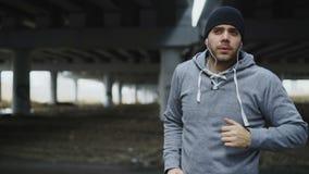 Przystojny sportive mężczyzna biegacza kładzenie na słuchawkach i początki biega przy miastową outdoors miasta lokacją w zimie zdjęcie wideo