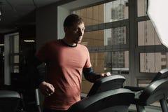 Przystojny sportowy mężczyzna ćwiczy na karuzeli w gym zdjęcia royalty free