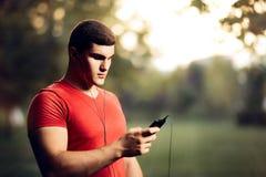 Przystojny Sportowy mężczyzna Jest ubranym słuchawki Trzyma Jego Smartphone Obrazy Royalty Free