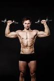 Przystojny sportowy mężczyzna pewnie patrzeje naprzód z dumbbells Fotografia Stock