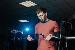 Przystojny sportowy mężczyzna trenuje bicepsa barbell w gym zdjęcia royalty free