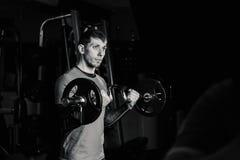 Przystojny sportowy mężczyzna trenuje bicepsa barbell w gym obraz royalty free