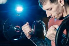 Przystojny sportowy mężczyzna trenuje bicepsa barbell w gym fotografia stock
