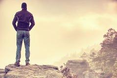Przystojny sportowy mężczyzna, turysta, pobyt na szczyt skale Dzika mgła obraz stock