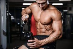Przystojny sprawność fizyczna model trzyma potrząsacza w gym zysku mięśniu Obrazy Royalty Free