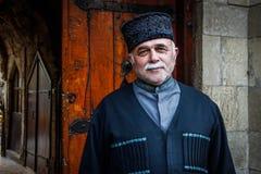 Przystojny starsza osoba mężczyzna ono uśmiecha się w krajowym Azerijskim kostiumu, kapeluszu i szarość wąsy, fotografia stock