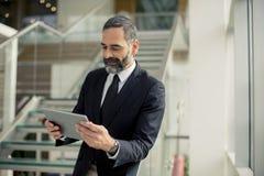 Przystojny starszy biznesmen z cyfrową pastylką w modren obrazy stock