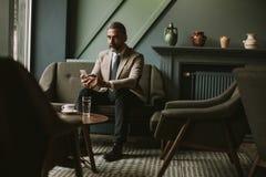 Przystojny starszy biznesmena pić kawowy i używać mobilnego pho obraz royalty free