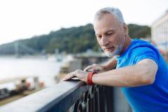 Przystojny starszy mężczyzna patrzeje jego mądrze zegarek Obraz Stock