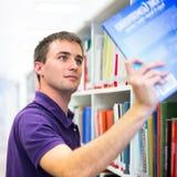 Przystojny student collegu w bibliotece zdjęcie royalty free