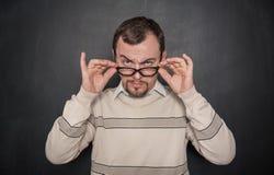 Przystojny surowy nauczyciel patrzeje ciebie na blackboard w eyeglasses obraz stock