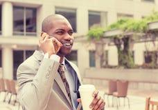 Przystojny szczęśliwy biznesmen opowiada na telefonie komórkowym pije kawę Obrazy Stock