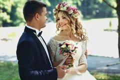 Przystojny szczęśliwy fornal i uśmiechnięta panna młoda w eleganckim bielu ubieramy wewnątrz Zdjęcia Stock