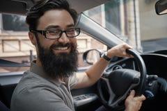 Przystojny, szczęśliwy mężczyzna jedzie samochód, fotografia stock