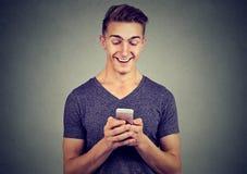 Przystojny szczęśliwy mężczyzna używa smartphone fotografia stock