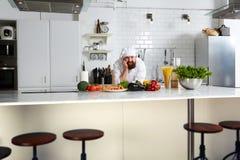 Przystojny szef kuchni w jednolitej pozyci na kuchni Fotografia Stock