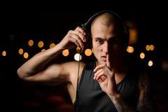 Przystojny tatuujący klub nocny DJ w hełmofonach czuje muzykę zdjęcia royalty free