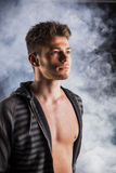 Przystojny twardy młody człowiek w ciemnym hoodie na dymiącym Zdjęcia Royalty Free