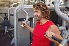 Przystojny uśmiechnięty mężczyzna pracuje na sprawności fizycznej maszynie przy gym Fotografia Royalty Free