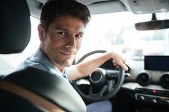 Przystojny uśmiechnięty męski klient bada jego nowego samochód obraz royalty free