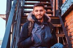 Przystojny uśmiechnięty młodego człowieka obsiadanie na schodkach outside obraz stock