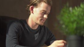Przystojny uśmiechnięty młody biznesmena obsiadanie w rzemiennym krześle przy jego biurkiem w jego biurze Mężczyzna zadawalający  zbiory wideo